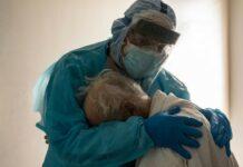 médico a abraçar idoso com Covid